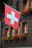 foto of foreshortening  - foreshortening of ancient building wooden facade with geranium and red swiss flag - JPG