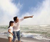 Постер, плакат: указывая отец и маленькая девочка глядя на пляже