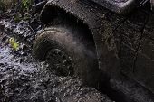 Offroad. Wheel With Little Cloud Of Smoke, Defocused. Fragfment Of Car Stuck In Dirt, Close Up. Dirt poster