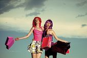 Prostitutes. Girls With Artificial Hair With Colorful Shopping Bag. Women In Wig With Makeup On Blue poster
