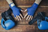 Mens Hands In Boxing Bandages And Boxing Gloves On A Wooden Bac poster