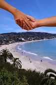 Engagement Couple holding hands with a beach background. A couple hold hands with a wedding ring and poster