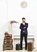 Macho Elegant On Thoughtful Face Standing Near Pile Of Vintage Suitcase. Luggage And Travelling Conc poster