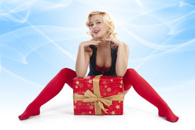 stock photo of up-skirt  - very attractive and sexy blond pin up with red christmas stocking and a big present box posing while on the floor - JPG