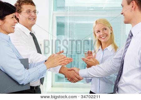 Successful businessmen handshaking while two females applauding after signing new contract