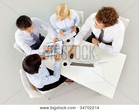 Group of business partners listening to mature woman pointing at document at meeting
