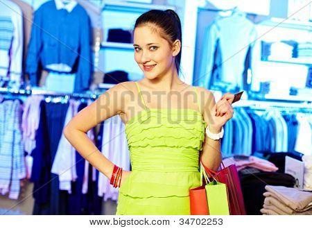 Retrato de uma mulher bonita com paperbags e olhando para câmera no departamento de vestuário de cartão plástico