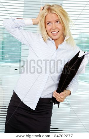 Sloppy businesswoman with briefcase scratching her head