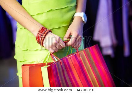 Image of shopaholic hands with three shopping bags