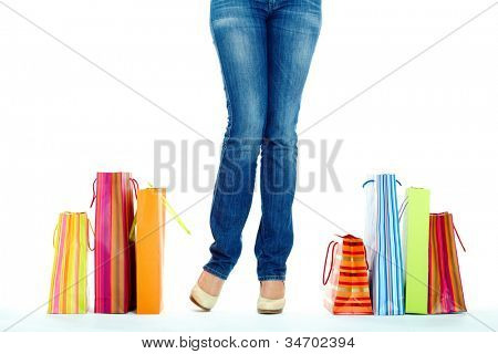 Image of shopaholic legs and shopping bags near by
