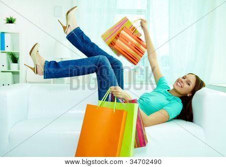 Retrato do cliente feliz com paperbags deitado no sofá e olhando para câmera