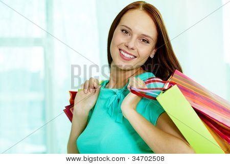 Retrato de menina feliz com paperbags olhando para câmera depois das compras