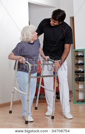 A therapist assisting a senior woman onto her walker.
