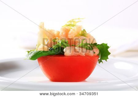 Halved tomato decorated with lettuce and fruit pap