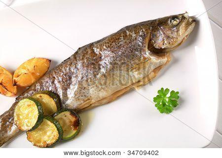 Trucha a la parrilla en un plato rectangular blanco con verduras