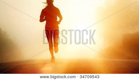 Pies de atleta corredor ejecutan en carretera. mujer fitness silueta sunrise jog entrenamiento concepto de bienestar.