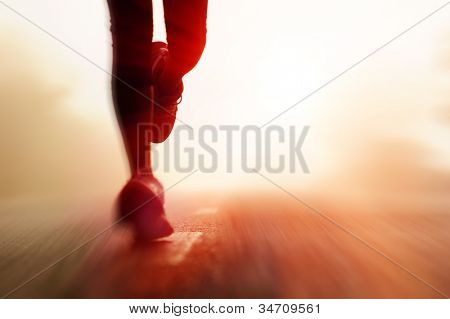 Runner athlete feet running on road. woman fitness silhouette sunrise jog workout wellness concept. with motion blur