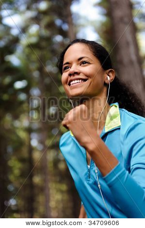 Portrait of a runner listening to music on headphones while running outdoors in a forest. healthy wellness fitness lifestyle.