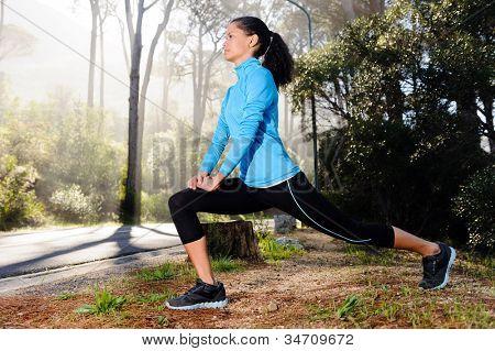 Mujer atlética calentamiento antes de su entrenamiento por la mañana en la carretera de montaña de bosque. Corredor formación ou