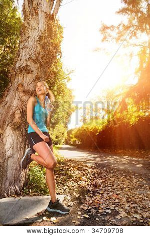 healthy happy fitness woman resting in suburb with water bottle after workout exercise session. vitality lifestyle runner.