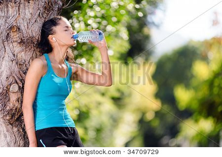 Athlete refreshing with bottle of water after running workout outdoors. marathon runner drinking, healthy active lifestyle.
