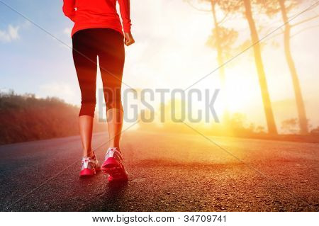 Athlete runner feet running on road closeup on shoe. woman fitness sunrise jog workout wellness concept.
