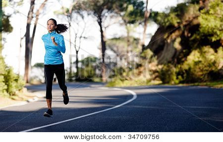 Fitness athlete training alone on a mountain road. Running endurance marathon woman exercising for healthy lifestyle and wellness. panorama with copyspace
