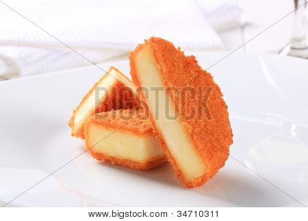 Fried and cut ermine cheese on a white plate