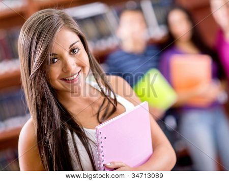 Beautiful female student smiling and holding a notebook