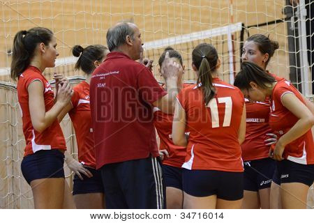KAPOSVAR, HUNGARY - MAY 18: Budai XI players listening to trainer at the final of the hungarian junior volleyball championship (Kaposvar  blue vs. Budai XI  red) , May 18, 2012 in Kaposvar, Hungary