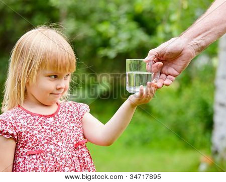 Adult giving mug of water to little girl outdoors