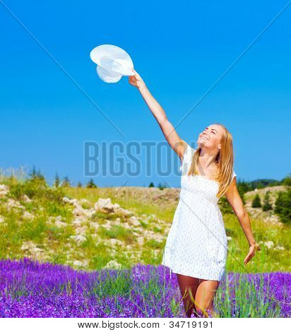 Cute girl dancing on lavender field, beautiful happy woman enjoying purple floral glade, pretty cheerful young lady walking on flower meadow, smiling female raised up hands with white hat in blue sky