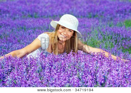 Pretty woman lying down on lavender field, beautiful happy female sitting on purple flowers meadow, cheerful smiling girl enjoying violet floral glade, portrait of young cute lady over lilac plant