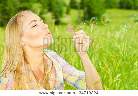 Pretty woman blowing soap bubbles in park, healthy beautiful female playing on green grass, carefree model relaxing outdoors, cute teen enjoying leisure time, vacation and summer holiday concept