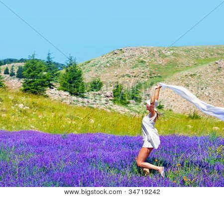Beautiful girl dancing on lavender field, cute teen running on purple flower meadow, pretty woman play with white scarf on floral glade, happy female enjoying nature, vacation, summer holiday concept