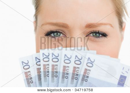 Close-up de um rosto de mulher escondido com notas de euro contra fundo branco