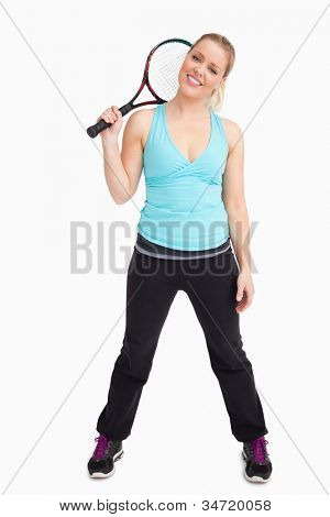 Woman standing with a tennis racket against white background