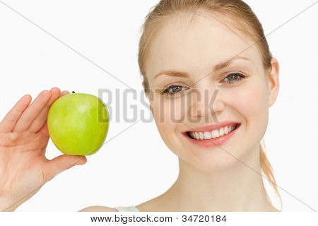 Blonde-haired girl smiling while holding an apple against white background
