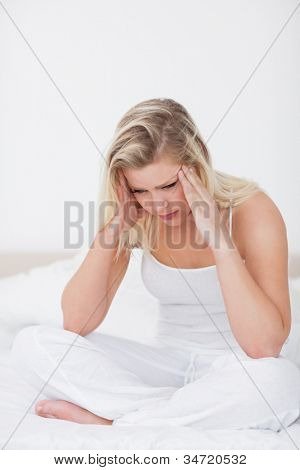 Blonde having a headache while sitting on a bed