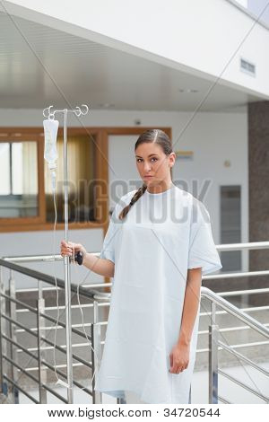 Female patient holding a drip stand in hospital ward