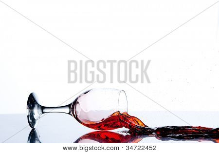 Glass on the floor with a red trickle flowing against a white background