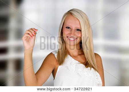 Woman holding keys in front of her new home