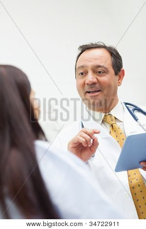 Smiling doctor talking with a patient while holding a tablet in an expression room