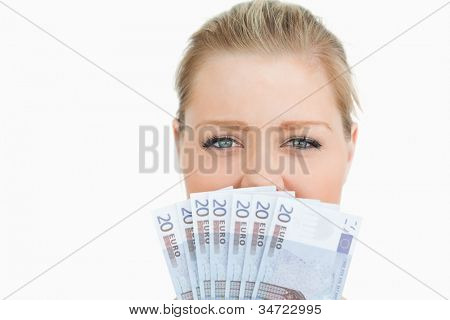 Woman hiding her mouse with her euros banknotes against white background