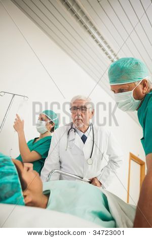 Doctor and surgeon looking at a female patient in hospital ward