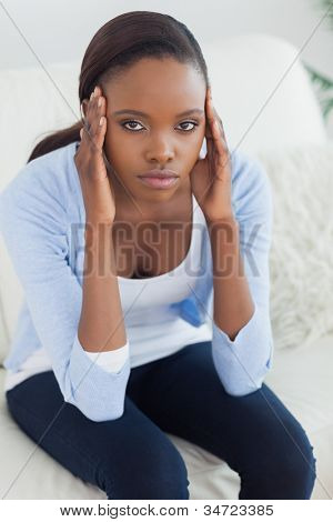 Black woman putting hands on temples in a living room