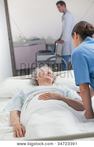 Nurse looking after an elderly patient in hospital hallway