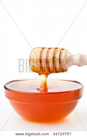 Honey dipper at horizontally  dropping a trickle of a honey against a white background