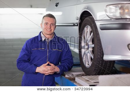 Front view of a mechanic next to a car in a garage