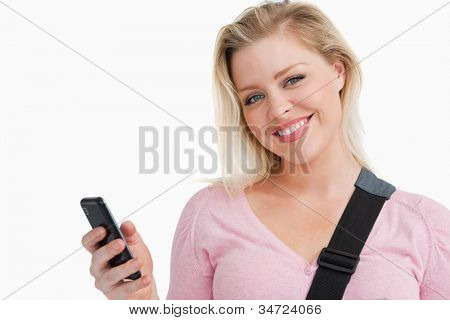 Blonde woman holding her mobile phone while writing a text against a white background
